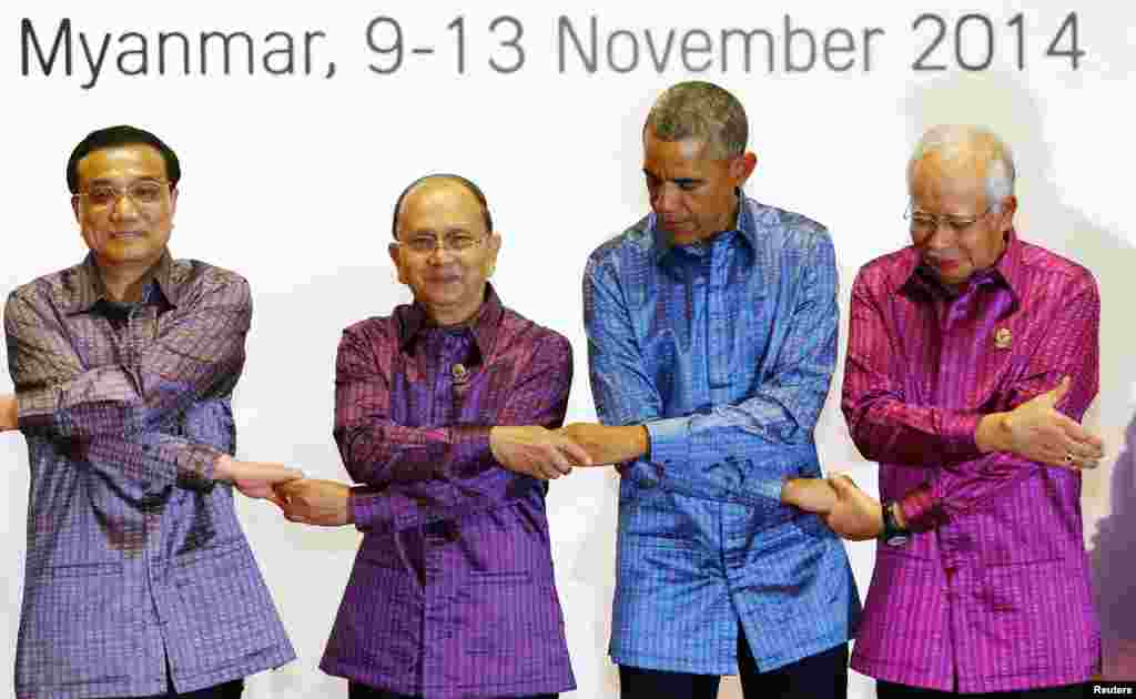Left to right, China's Premier Li Keqiang, Myanmar's President Thein Sein, U.S. President Barack Obama and Malaysia's Prime Minister Najib Razak hold hands as they pose for family photo before the gala dinner at the 25th ASEAN Summit in Myanmar.