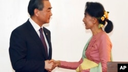 Leader of the National League for Democracy party (NLD) and Myanmar's new foreign minister, Aung San Suu Kyi, shakes hands with Chinese Foreign Minister Wang Yi, left in Naypyitaw, Myanmar, April 5, 2016.