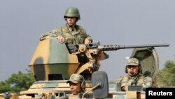 Turkish soldiers are seen on an armoured personnel carrier as part of a Turkish military convoy travelling on a main road leading to the southeastern Turkish city of Kilis July 30, 2012
