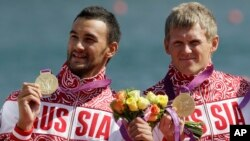 Russia's Yury Postrigay, right, and Alexander Dyachenko, left, show the gold medals they won in the men's kayak double 200m in Eton Dorney, near Windsor, England, at the 2012 Summer Olympics, Aug. 11, 2012. Dyachenko was among the five canoeists named in a recent report in 2016 by the World Anti-Doping Agency, alleging a state-sponsored doping cover-up.