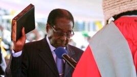 Zimbabwean President Robert Mugabe holds the bible during his inauguration in Harare, August 22, 2013. - AP