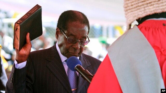 Zimbabwean President Robert Mugabe holds the bible during his inauguration, Harare, Aug. 22, 2013.