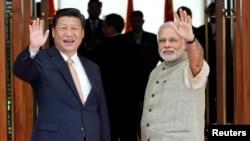 Presiden China Xi Jinping (kiri) dan dan PM India Narendra Modi sebelum melakukan pertemuan di Ahmedabad, India (17/9).