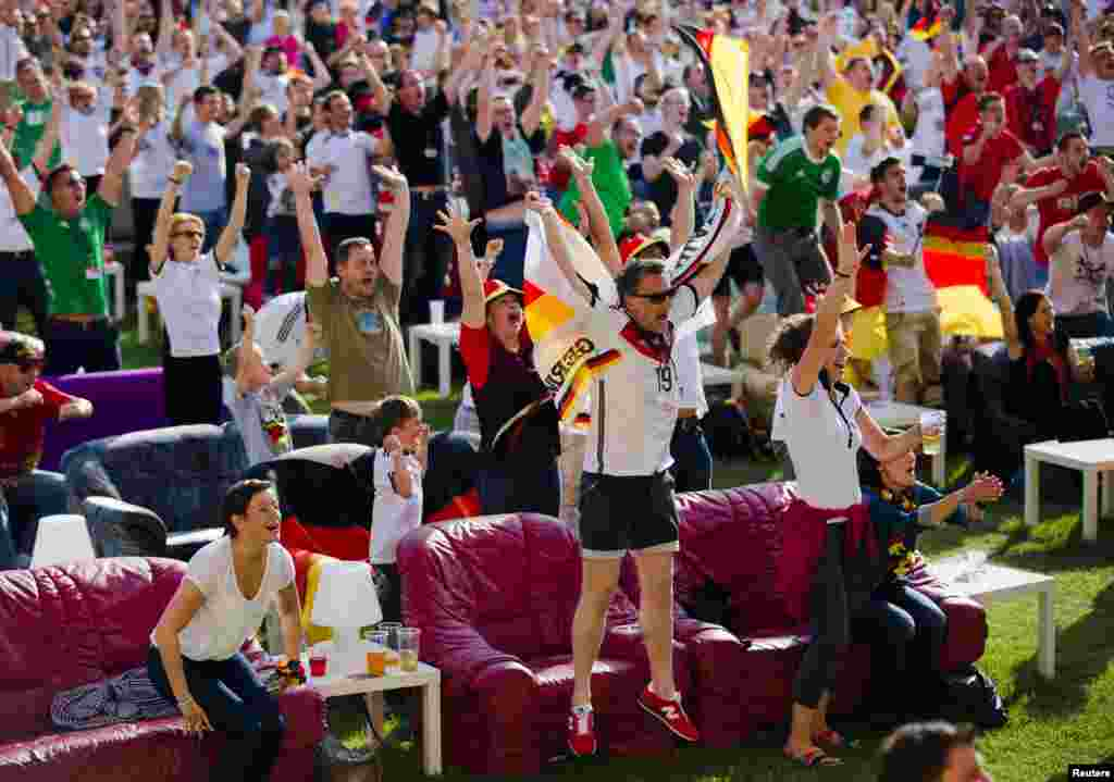 People celebrate a German goal as they watch the team playing against Portugal in a World Cup soccer match at a public viewing event at the Alte Foersterei stadium in Berlin.