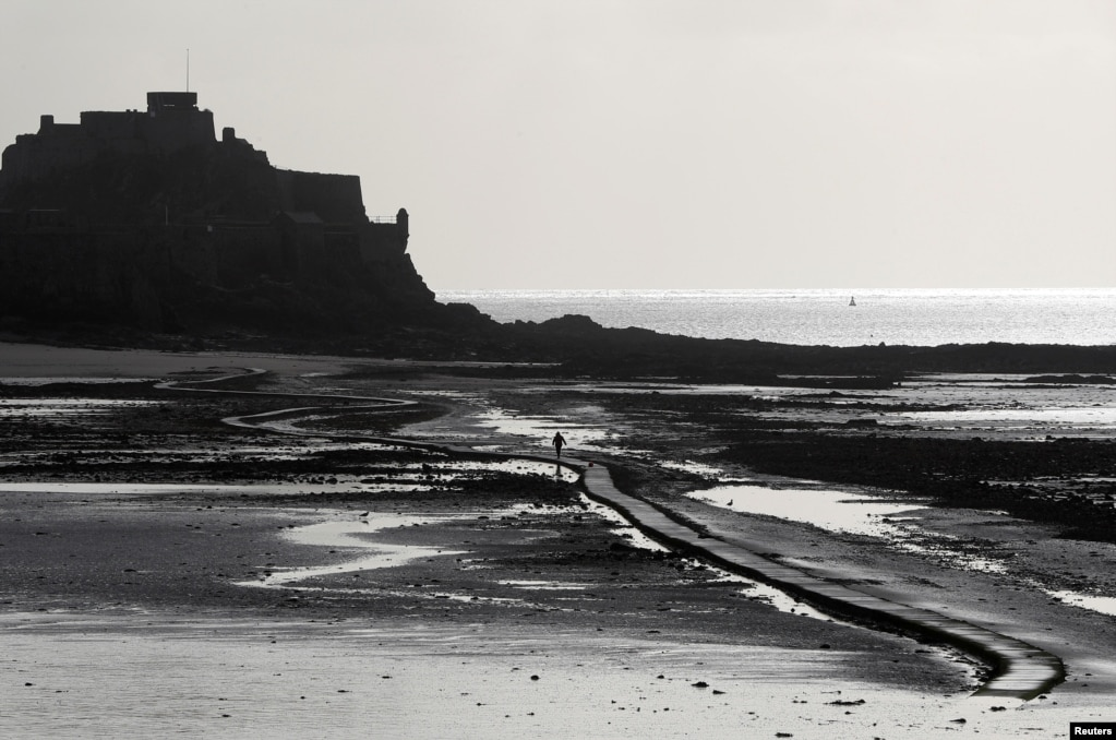 A man walks out on the tidal causeway to Elizabeth Castle in St. Helier, Jersey, Britain.