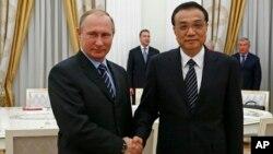 8일 러시아 모스크바를 방문한 리커창 중국 총리(오른쪽)가 블라디미르 푸틴 러시아 대통령과 만나 악수하고 있다.