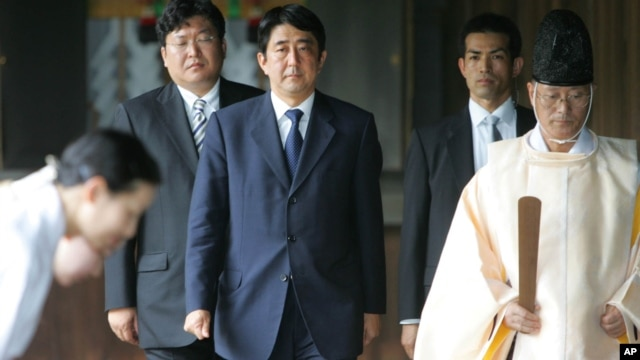 Japanese Prime Minister, Shinzo Abe is led by a Shinto priest during his visit to the Yasukuni shrine in 2005 where Japan's war dead including high-ranking war criminals have been enshrined. (File Photo)