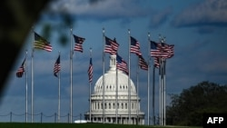 FILE - The dome of the U.S. Capitol building is seen behind a row of U.S. flags in Washington, April 10, 2020.