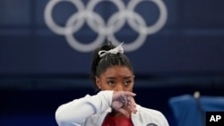 Simone Biles says she wasn't in right 'headspace' to compete and withdrew from gymnastics team final to protect herself.