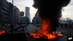 Smoke billows over burning barricades in front of the new ECB headquarters in Frankfurt, Germany, Wednesday, March 18, 2015.