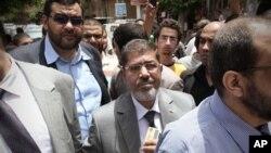 ຜູ້ສະມັກປະທານາທິບໍດີຂອງພັກພະລາດອນພາບມຸສລິມ ທ່ານ Mohammed Morsi (ກາງ) ເຂົ້າແຖວຖ້າປ່ອນບັດ ທີ່ເມືອງ Zakazik 80 ຫຼັກກິໂລແມັດຫ່າງຈາກກຸງໄຄໂຣໄປທາງທິດເໜືອ (23 ພຶດສະພາ 2012)