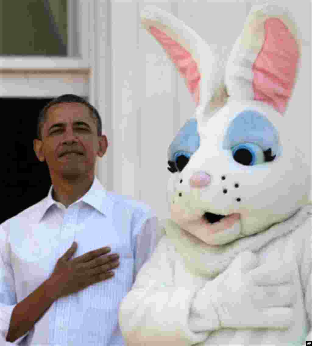 President Barack Obama stands next to the Easter Bunny during the singing of the National Anthem, at the White House in Washington, Monday, April 9, 2012, during the annual Easter Egg Roll. (AP Photo/Carolyn Kaster)