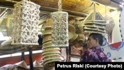 Pembeli melihat-lihat aneka jenis perabot rumah tangga dari bambu (Foto: VOA/Petrus Riski).