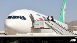 """Penumpang turun dari pesawat milik maskapai Iran """"Mahan Air"""" di bandara Kabul (15/9)."""