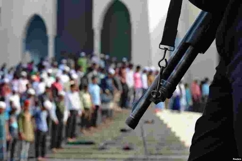 People take part in Friday prayers as members of the police stand guard in Dhaka, Bangladesh. The country is set to vote in nationwide polls on Sunday.