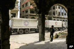 This photo released by the Syrian Arab Red Crescent, show Syrian Red Crescent trucks carrying humanitarian aid to be distributed in Douma, eastern Ghouta, a suburb of Damascus, March 15, 2018.