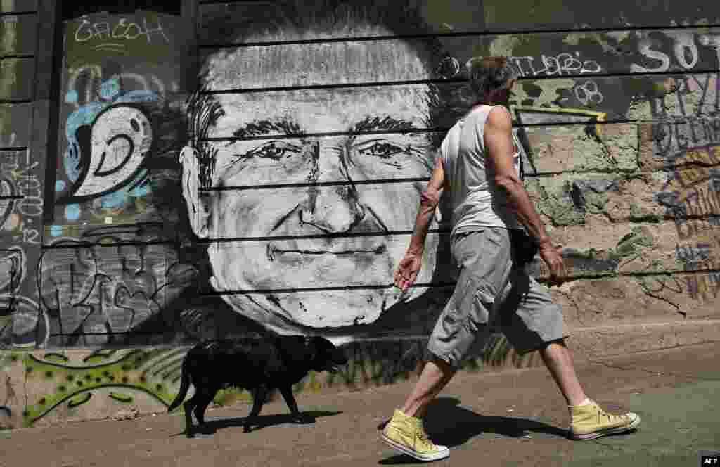 A man with his dog walk past a mural depicting actor Robin Williams in downtown Belgrade, Serbia. Unknown artists drew the academy award-winning actor and comedian below a bridge to pay a tribute following the news that he had been found dead of an apparent suicide at the age of 63.