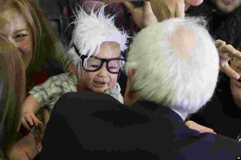 Democratic presidential candidate Sen. Bernie Sanders, I-Vt., right, meets 3-month-old Oliver Lomas, of Venice, California, who was dressed as Sanders during a rally at Bonanza High School in Las Vegas, Nevada, Feb. 14, 2016.