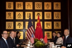 FILE - Chinese Vice Premier Liu He, right, sits with U.S. Trade Representative Robert Lighthizer, second from left, and Treasury Secretary Steven Mnuchin, left, before the start of talks at the Xijiao Conference Center in Shanghai, July 31, 2019.