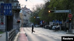 A man crossing a street as Croatia is stepping up measures to fight the coronavirus disease (COVID-19) outbreak, in Zagreb, Croatia March 21, 2020. REUTERS/Antonio Bronic/