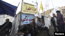 Para pengunjuk rasa penentang Presiden Morsi beristirahat di depan tenda yang diberi nama 'Partai Revolusi' di Lapangan Tahrir, Kairo (17/12).