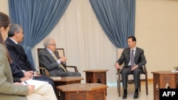 A handout picture released by the official Syrian Arab News Agency (SANA) on Oct. 30, 2013, shows Syrian President Bashar al-Assad (R) and Ministers meeting with U.N.-Arab League peace envoy Lakhdar Brahimi (2ndR) in Damascus.