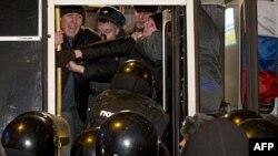 Nhiều người biểu tình bị lôi đi bằng vũ lực, điệu lên những chiếc xe van của cảnh sát chực sẵn gần hiện trường, Moscow, 31/12/2011