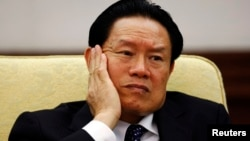 Then China's Public Security Minister Zhou Yongkang reacts as he attends the Hebei delegation discussion sessions at the 17th National Congress of the Communist Party of China at the Great Hall of the People, in Beijing October 16, 2007