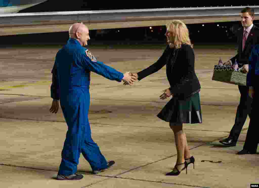 Dr. Jill Biden, wife of Vice President Joe Biden, right, greets Expedition 46 Commander Scott Kelly of NASA, left, after he landed at Ellington Field in Houston, Texas after his return to Earth.
