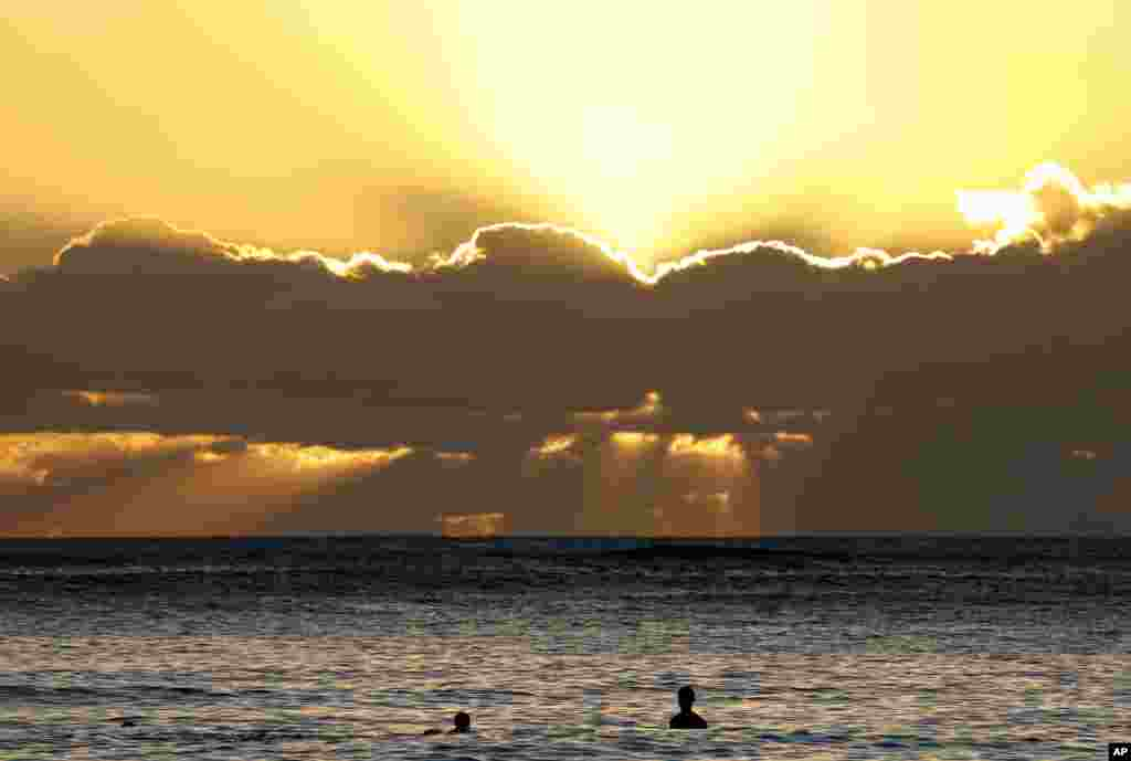 Swimmers watch the sunset behind clouds over the Pacific Ocean seen from Waikiki Beach in Honolulu, Hawaii,  Dec. 31, 2016, the last sunset of 2016.