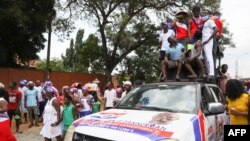 FILE - Supporters of the New Patriotic Party cheer on the street after President Nana Akufo-Addo filed his nomination forms for the 2020 presidential election at the Electoral Commission Head Office in Accra, Ghana, Oct. 6, 2020.