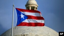 The Puerto Rican flag flies in front of Puerto Rico's Capitol in San Juan, July 29, 2015.