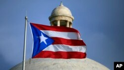The Puerto Rican flag flies in front of Puerto Rico's Capitol in San Juan, July 29, 2015.