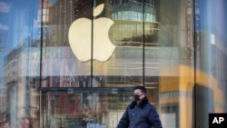 A man wears a face mask as he walks past an Apple store that is temporarily closed due to health concerns in Beijing, Tuesday, Feb. 4, 2020. Apple announced that it will temporarily close all of its stores in China due to a virus outbreak. (AP Photo/Mark