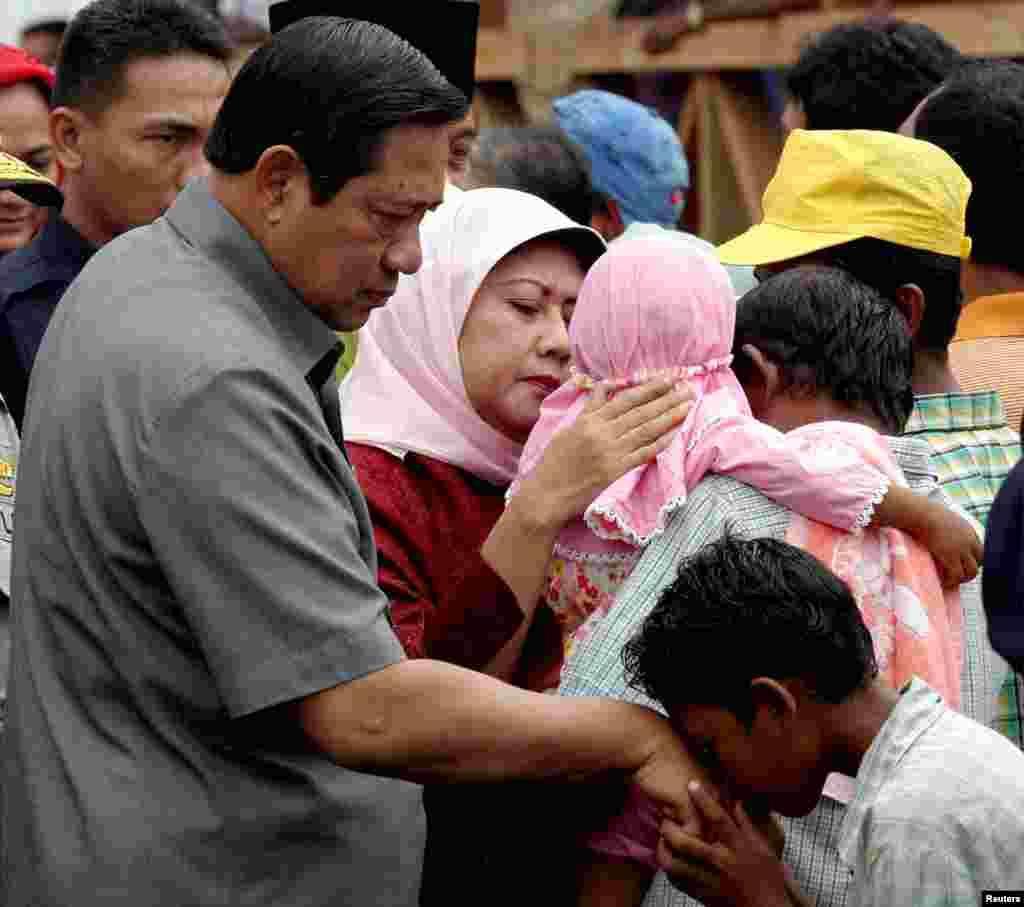 Ibu Ani Yudhoyono memeluk seorang anak prempuan di Banda Aceh setelah bencana gempa dan tsunami yang melanda Aceh, 19 Februari 2005. (Foto: Tarmizi Harva/Reuters)