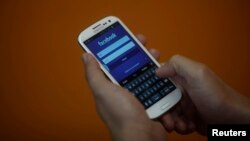 File - A smartphone user logs into his Facebook account.
