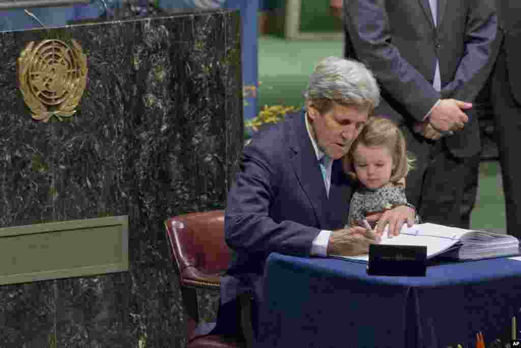 U.S. Secretary of State John Kerry holds his granddaughter as he signs the Paris Agreement on climate change at U.N. headquarters in New York .