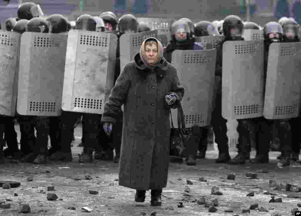 A woman walks from police officers as they block a street during unrest in central Kyiv, Jan. 21, 2014.