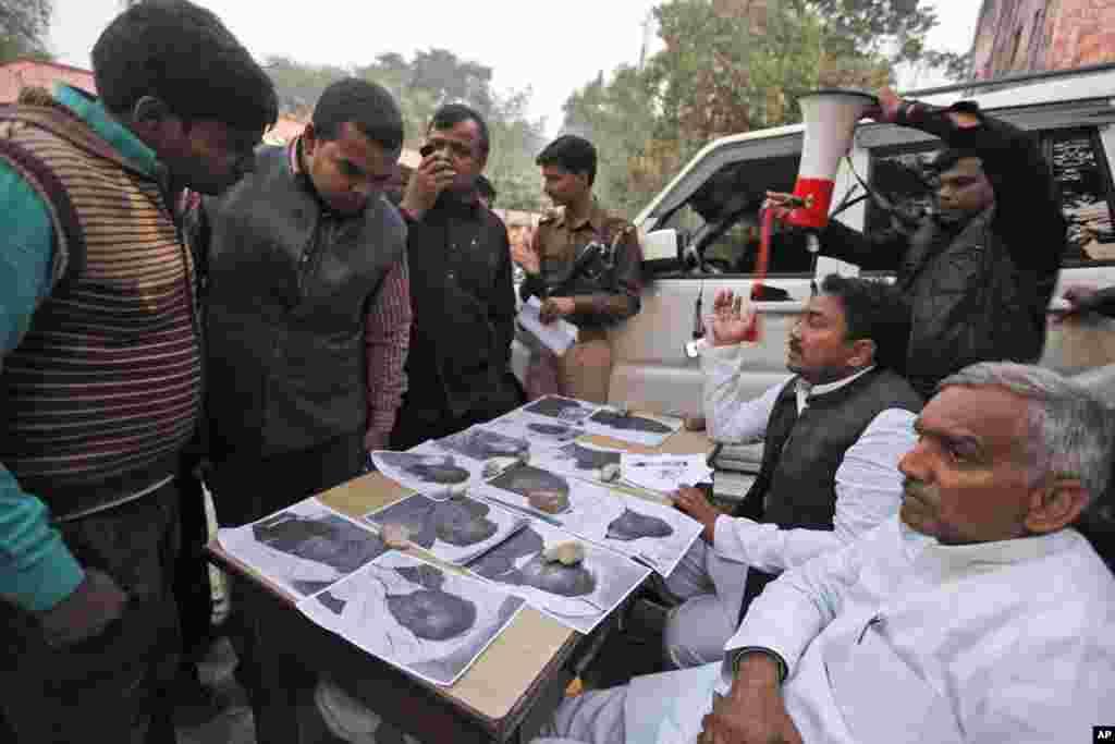 Thân nhân những người bị nạn nhìn ảnh của các nạn nhân đã chết trong vụ giẫm đạp bày ra ở bên ngoài một nhà xác bệnh viện ở Allahabad.