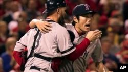 El lanzador relevista Koji Uehara es abrazado por su cátcher, David Ross, luego de que los Medias Rojas ganaran el quinto juego de la Serie Mundial de béisbol.
