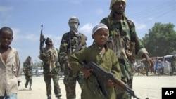 Một bé trai và các chiến binh khác của nhóm Hồi giáo al-Shabab luyện tập quân sự