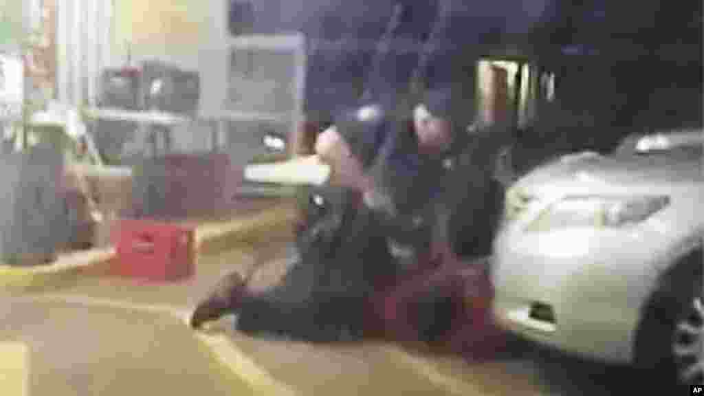 Alton Sterling maintenu au sol par par deux officiers de police de Baton Rouge. On peut voir l'un des policiers un pistolet à la main, à Baton Rouge le 5 juillet 2016.