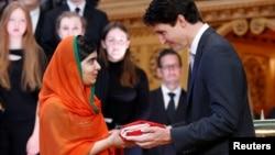 Le Premier ministre canadien Justin Trudeau offrant le drapeau canadien à Malala Yousafzai à la librairie du Parlement, à Ottawa, le 12 avril 2017.