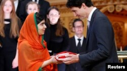 Canada's Prime Minister Justin Trudeau (R) presents Pakistani Nobel Peace Prize laureate Malala Yousafzai with a Canadian flag during a ceremony in the Library of Parliament on Parliament Hill in Ottawa, Ontario, Canada, April 12, 2017. Yousafzai also became an honorary Canadian citizen.