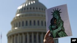 FILE - An activist holds up a pro-refugee image during a demonstration outside of the U.S. Capitol in Washington, Oct. 15, 2019.