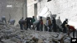 Warga Iran memeriksa reruntuhan bangunan yang hancur akibat serangan udara di Aleppo, Suriah (27/4).