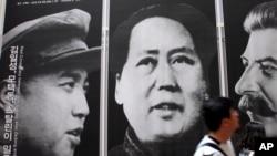 资料照片:在首尔一家韩战展览馆,游人走过战时三名共产党领袖金日成、毛泽东和斯大林的像。