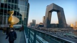 一名戴着口罩的男子在中国官媒中央电视台总部大楼附近的观景台行走。(2021年2月4日)