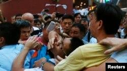 Một người biểu tình ủng hộ dân chủ (giữa) bị một người biểu tình chống phong trào Chiếm Trung Tâm (phải) túm tại quận mua sắm Mongkok ở Hong Kong, 3/10/2014.