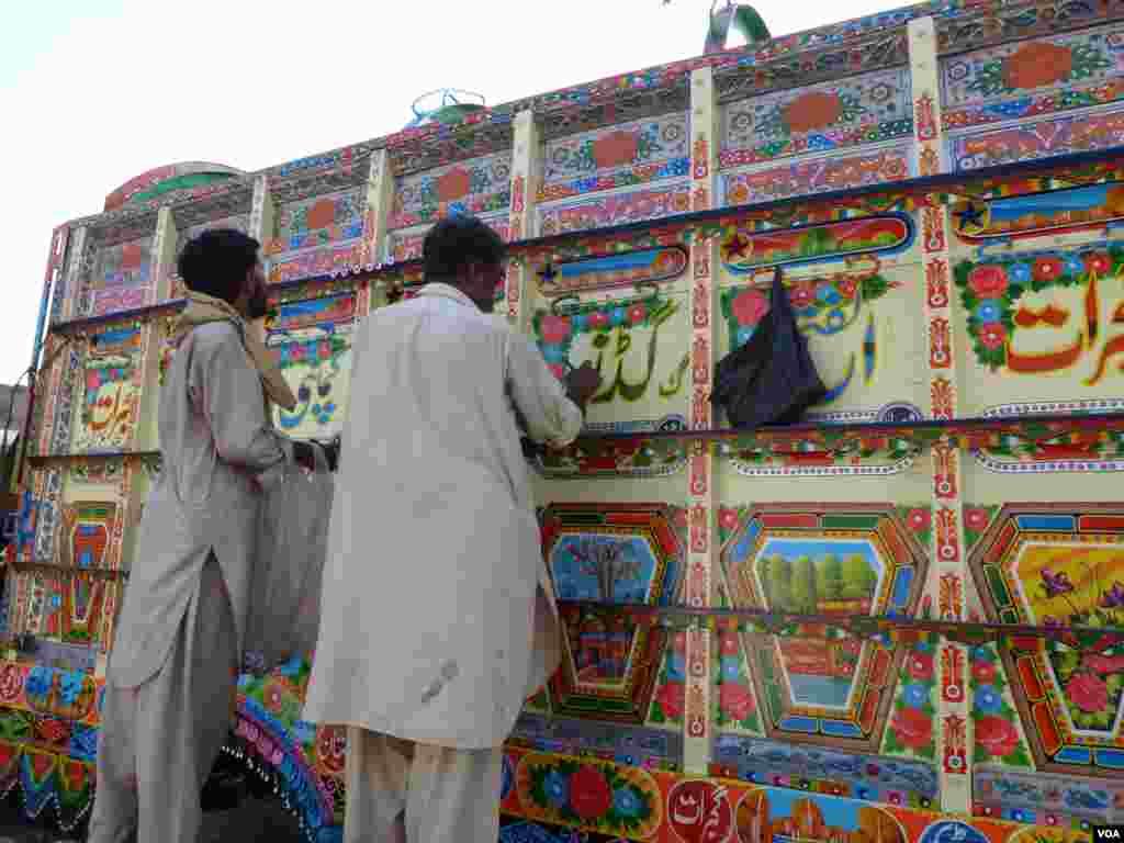 Men paint a bus, Islamabad, Pakistan, July 10, 2012. (S. Gul/VOA)